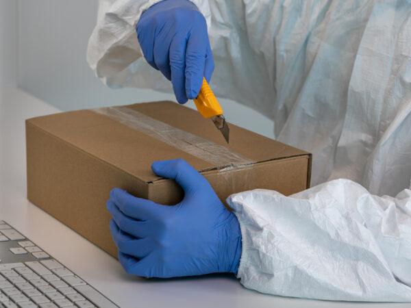 Läkare som skyddsdräkt som packar upp covid 19 test